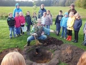 Gespannt lauschen die Kinder der Anleitung von Jörg Rohwehl vom Aukruger Bund beim pflanzen eines Musterbaumes.